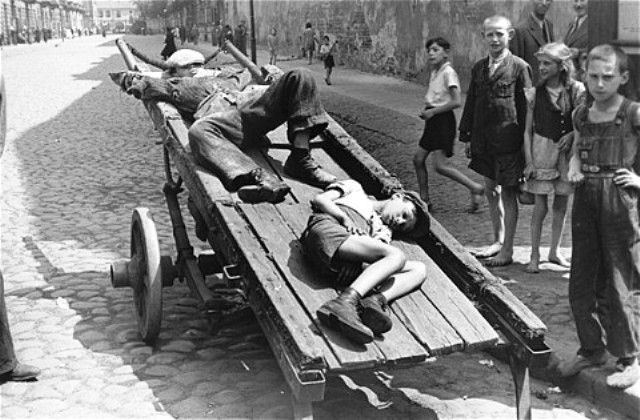 Two destitute boys sleep on a cart parked on a street in the Warsaw ghetto
